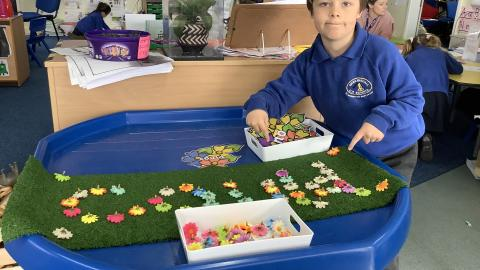 Child spelling word using flower heads