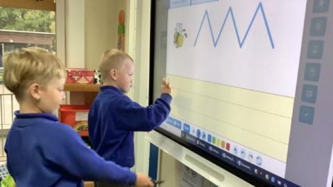 two children practising their handwriting on an interactive whiteboard