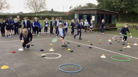 children taking it in turns to hit a beanbag into a hoop