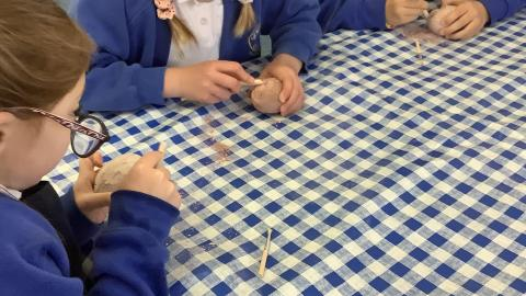 children chipping away at a salt dough shaped egg